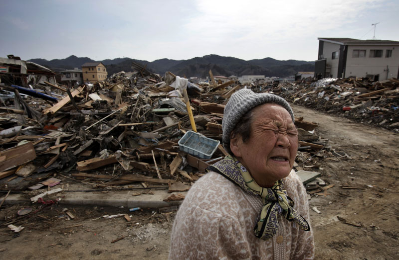 A woman, whose house was washed away, emotionally talks as debris scatter around Shinhamacyo area in Kesennuma, Miyagi, Japan on March 29, 2011after massive earthquake and tsunami hit northern Japan. More than 10,000 were killed and more than 17,000 are still missing by the disaster hit on March 11. Photo by Kuni Takahashi